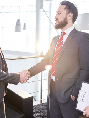 Profile view of confident entrepreneur wearing elegant suit greeting his business partner with firm handshake, his pretty assistant manager standing next to him, lens flare